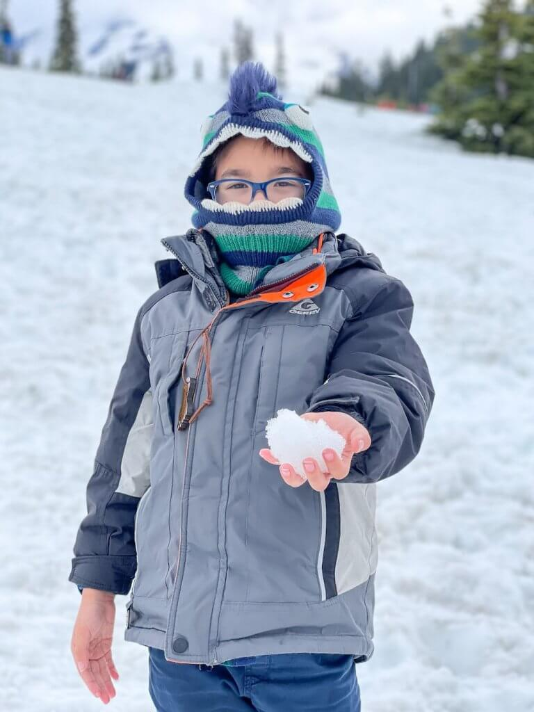 Yes, there was still snow in May at Mount Rainier National Park! Image of a boy holding a snowball.