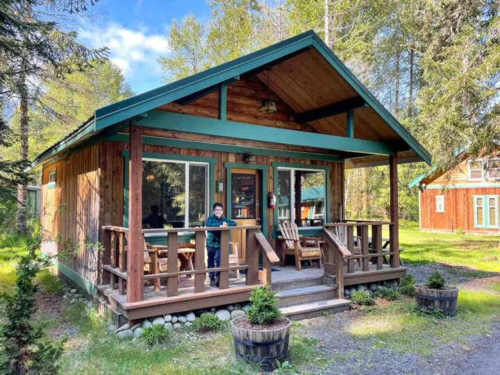 Find out why we think Stone Creek Lodge is one of the best Mt Rainier cabins for families. Image of a kid posing on the porch of a Mount Rainier cabin.