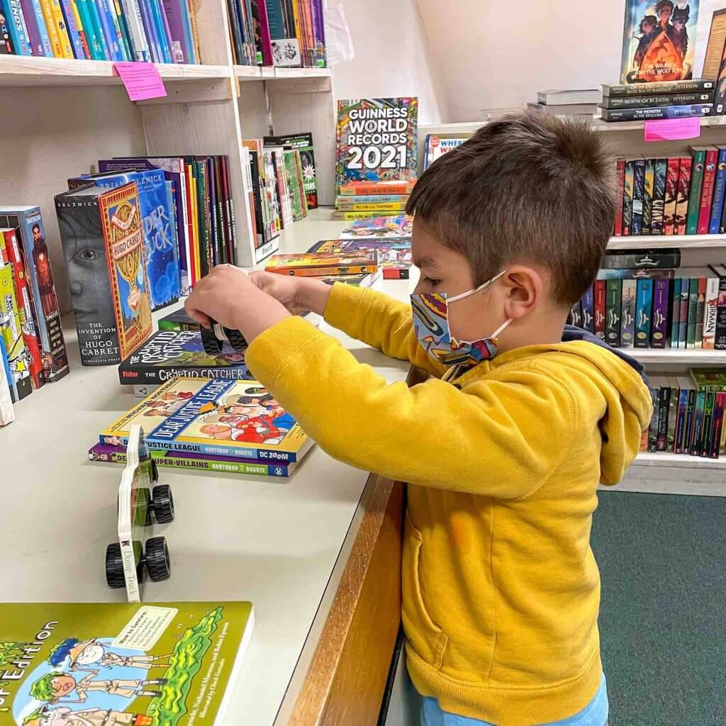 We love supporting independent book stores when we travel. Image of a boy looking at books at A Good Book in Sumner WA.