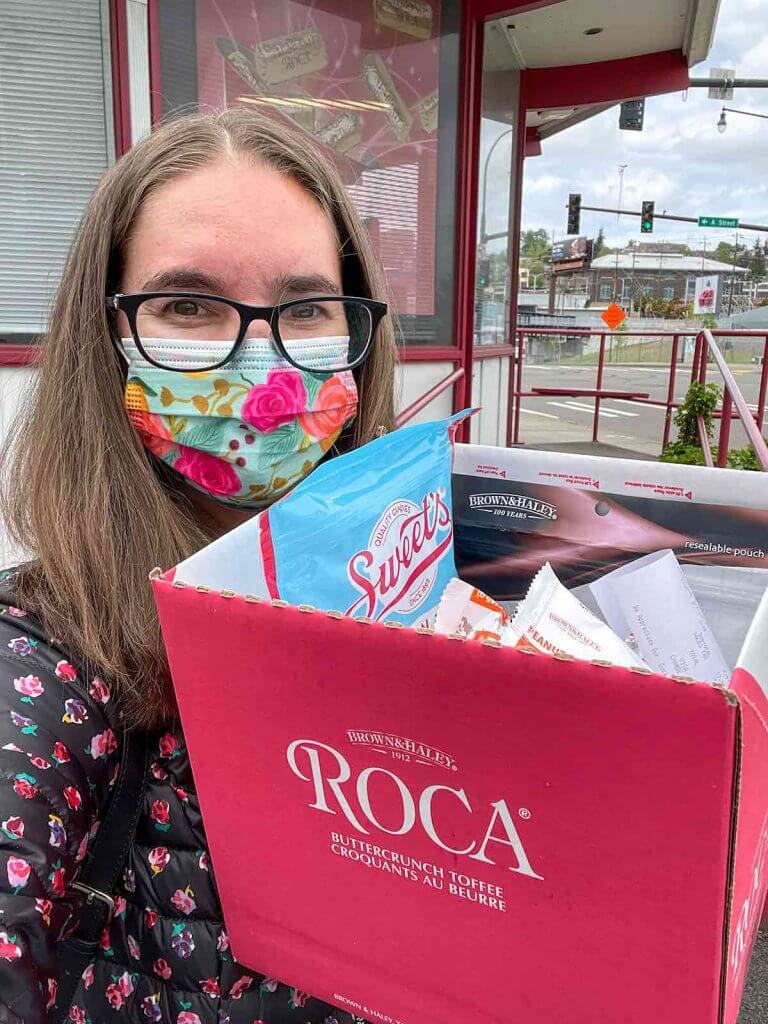 The Almond Roca Factory Store in Tacoma is always worth a stop. Image of a woman taking a selfie while holding a big box of candy.