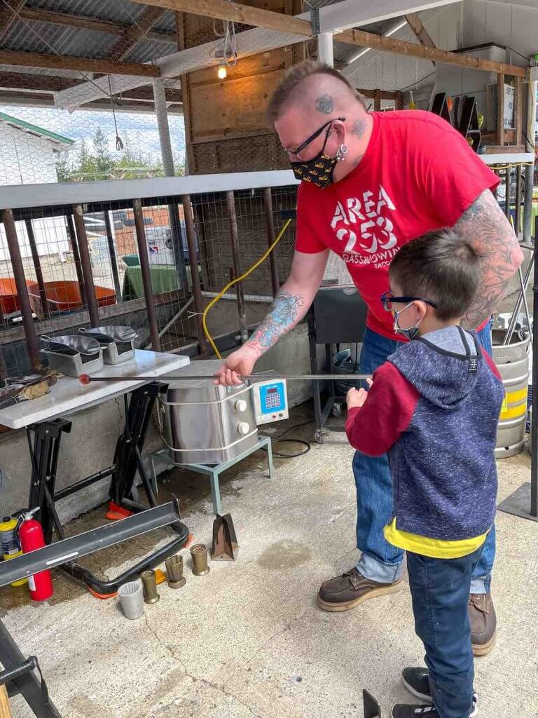 Area 253 is a cool glassblowing studio in Tacoma WA. Image of a boy and adult doing glassblowing outside at Maris Farms.