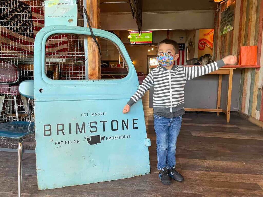 Brimstone PNW Smokehouse is one of the top Gig Harbor restaurants for families. Image of a boy posing next to a truck door with the name of the Gig Harbor restaurant on it.