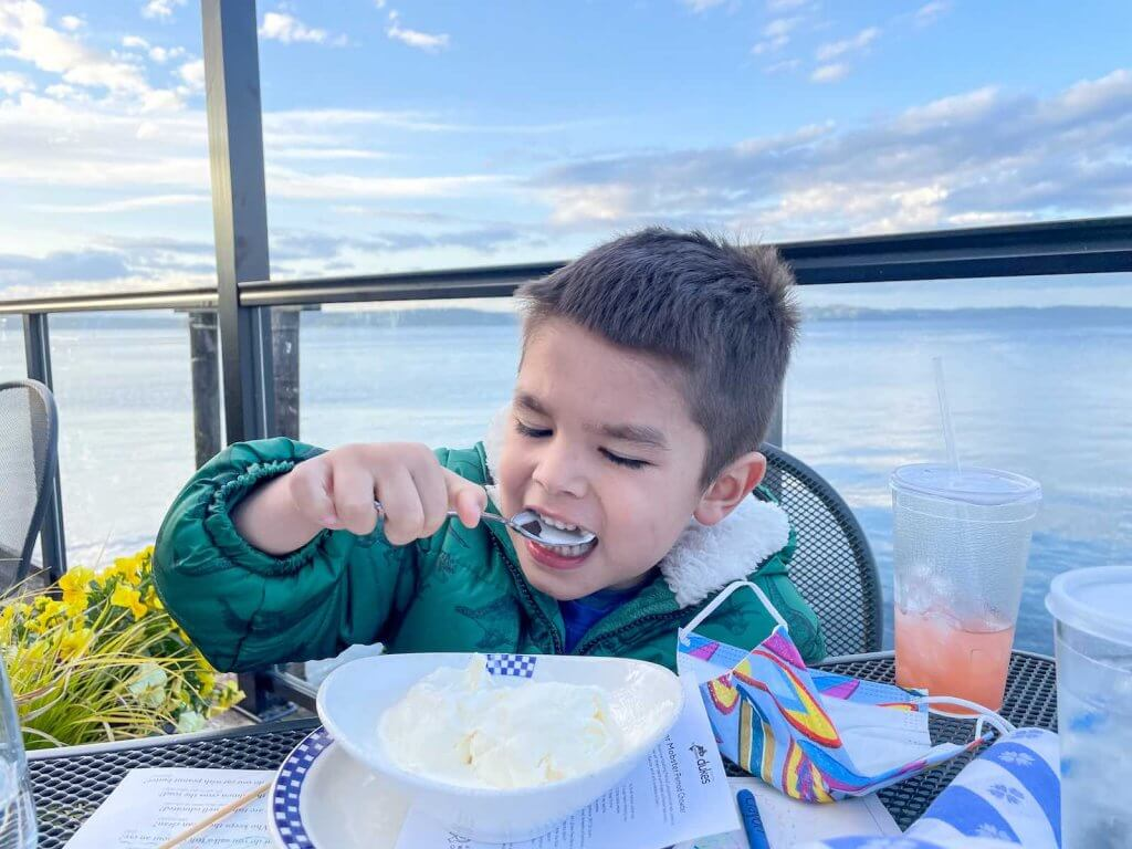 One of the best Tacoma restaurants is Duke's Seafood on the Tacoma waterfront. Image of a boy eating ice cream at Duke's Seafood.