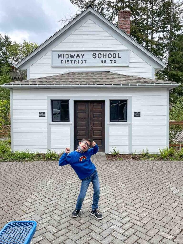 Visiting the Harbor History Museum is a top thing to do in Gig Harbor Washington. Image of a boy doing a funny pose outside of a one room school house.