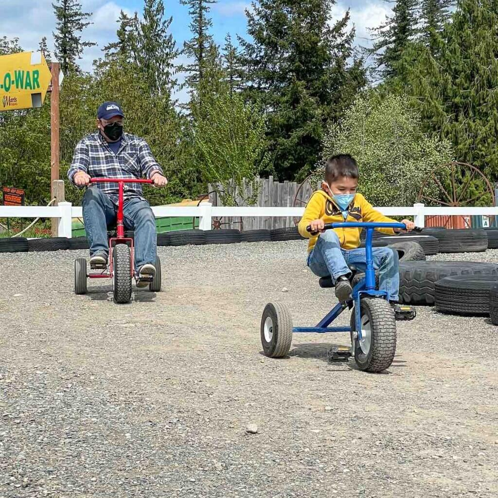 Maris Farms is one of the best places to go in South Sound. Image of a dad and son each riding tricycles at Maris Farms in Buckley, WA.
