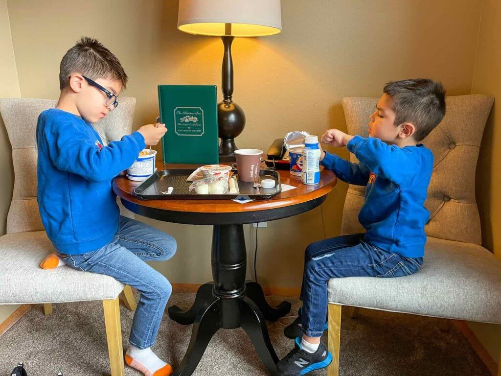 The Maritime Inn in Gig Harbor offers an extensive grab and go breakfast. Image of two boys sitting in a hotel room eating Frosted Flakes.