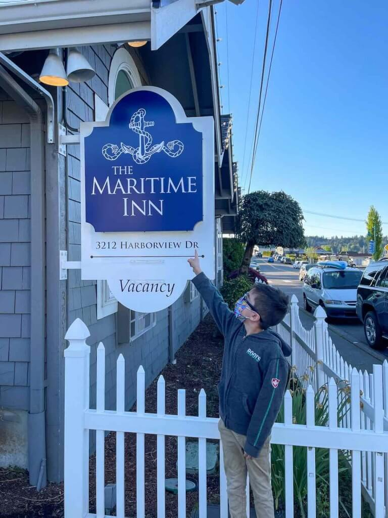 The Maritime Inn is one of the best places to stay in Gig Harbor. Image of a boy pointing at the Maritime Inn exterior sign.