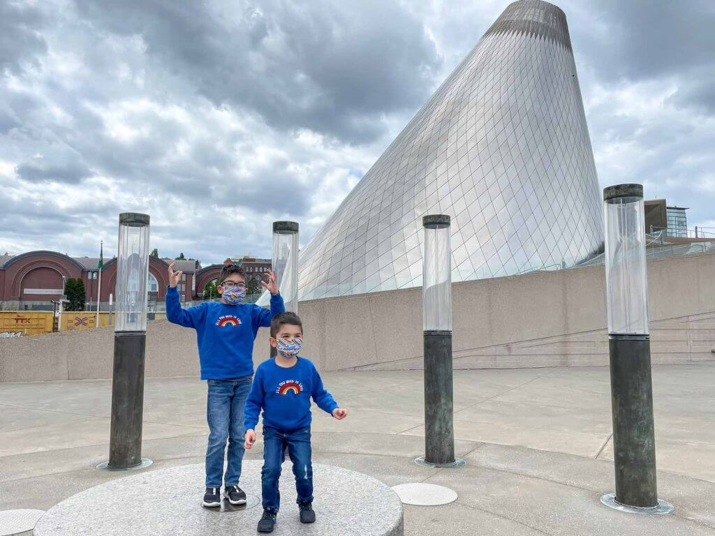 The Museum of Glass is a top thing to do in Tacoma with kids. Image of two boys dancing in front of the Tacoma Museum of Glass.