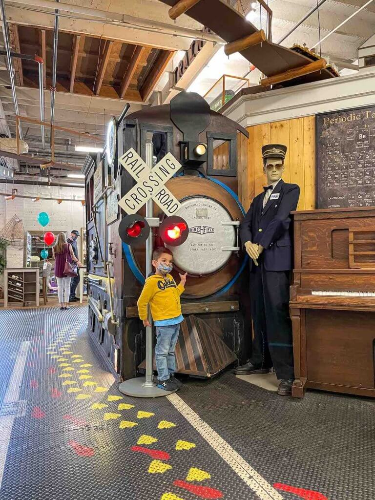 Definitely head to the Old Cannery Furniture Store in Sumner WA. Image of a boy posing in front of a giant train display.