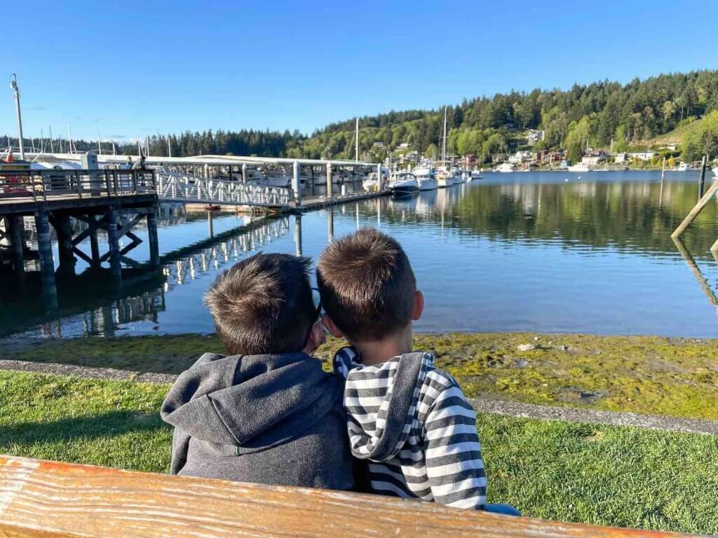 You'll definitely want to check out Skansie Park while you walk along the Gig Harbor waterfront. Image of two boys sitting on a bench looking at the waterfront in Gig Harbor, which is one of the best Weekend Getaways in Washington.