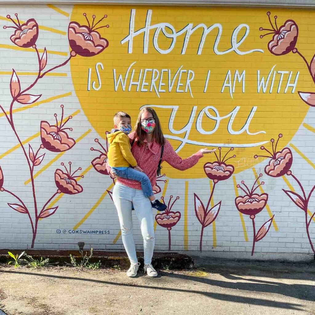 """There are lots of amazing murals in Sumner like this one. Image of a mom and boy posing in front of a mural that says """"home is wherever I am with you"""""""