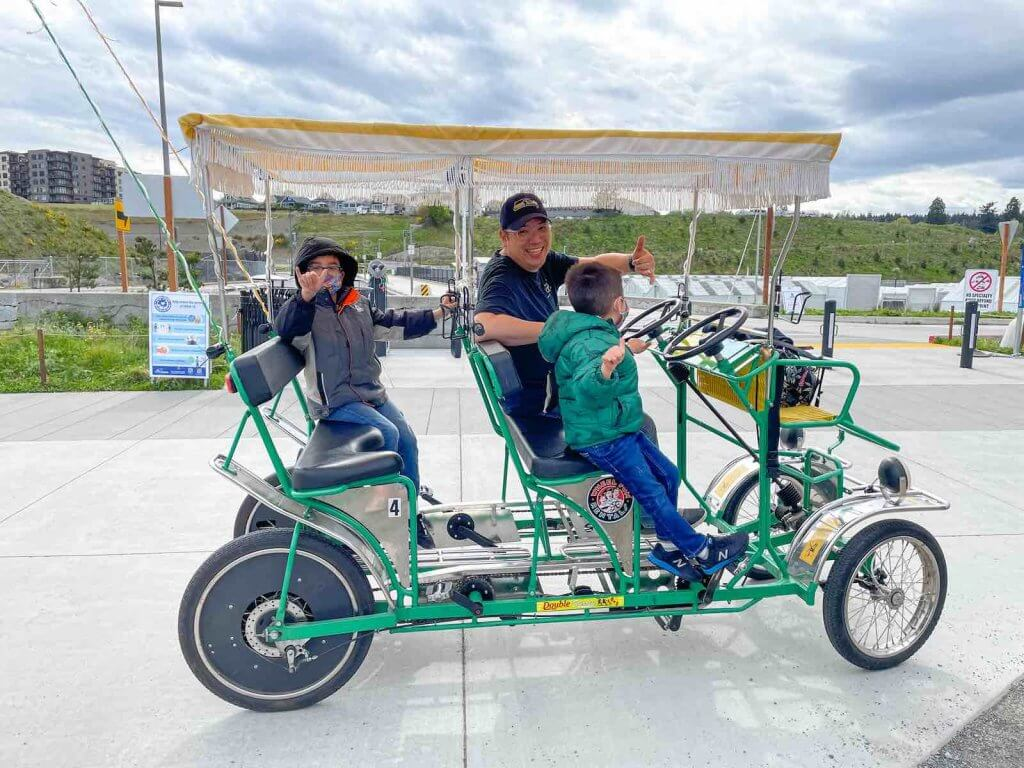 One of the best things to do at Point Ruston Tacoma is rent surrey bikes. Image of a dad and two boys posing in a green surrey bike at Point Ruston.