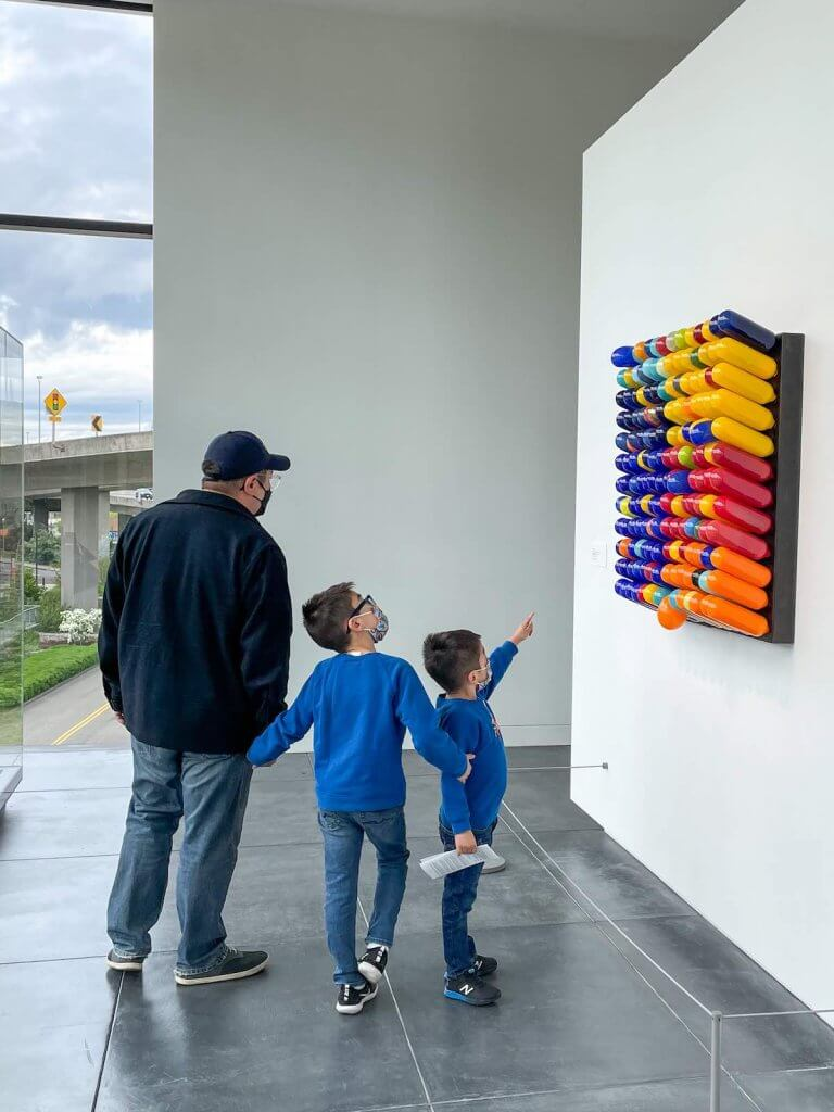 The Tacoma Art Museum is one of the best places to go in Tacoma WA. Image of a dad and two boys looking at an art display.