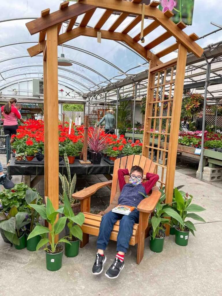 Windmill Gardens is a fun place to go in Sumner WA for plants. Image of a boy relaxing in a chair.