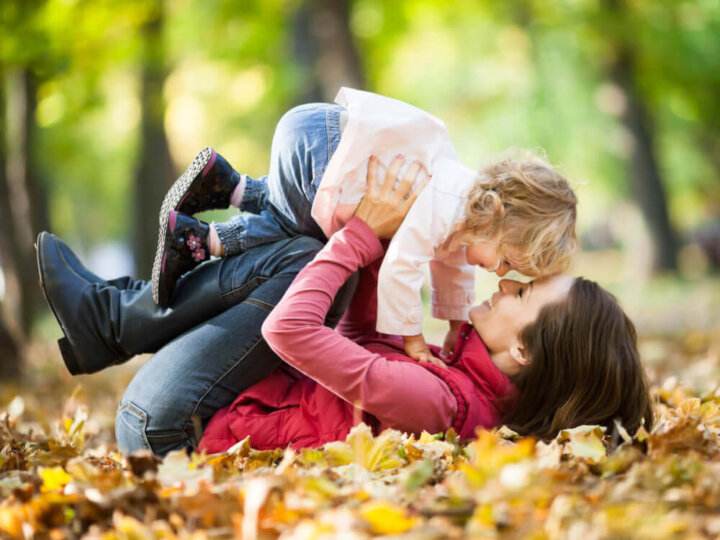 Get my free fall bucket list and free fall scavenger hunt printables by top Seattle blog Marcie in Mommyland. Image of a mom and toddler playing in the fall leaves.