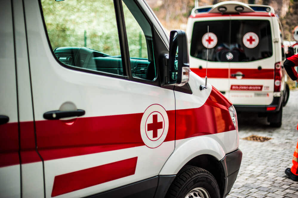 Hawaii travel insurance can provide you with emergency assistance in Hawaii. Image of two ambulances parked on a road.