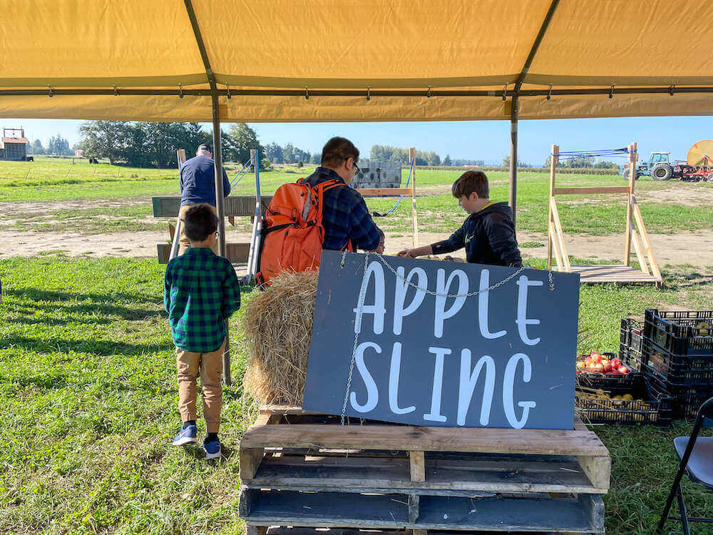 Image of the Apple Sling sign with the catapults in the background.