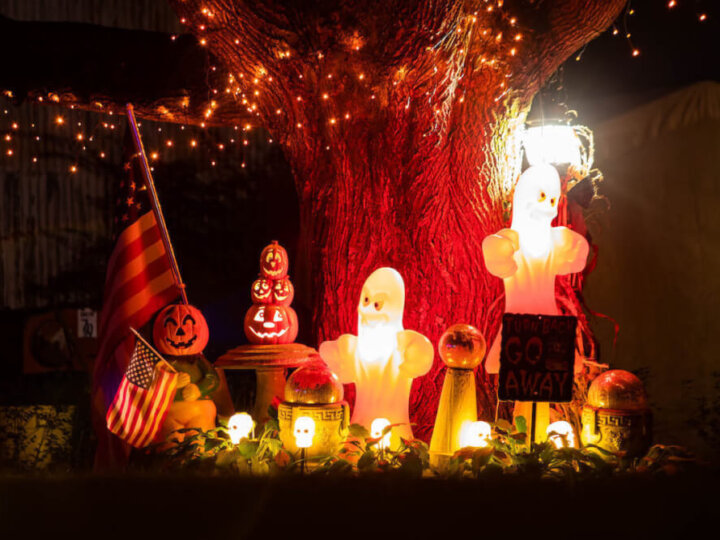 Find out the best Halloween lights to get for a spooky yard this Halloween season. Image of pumpkins, a lit up ghost and orange lights on a tree.
