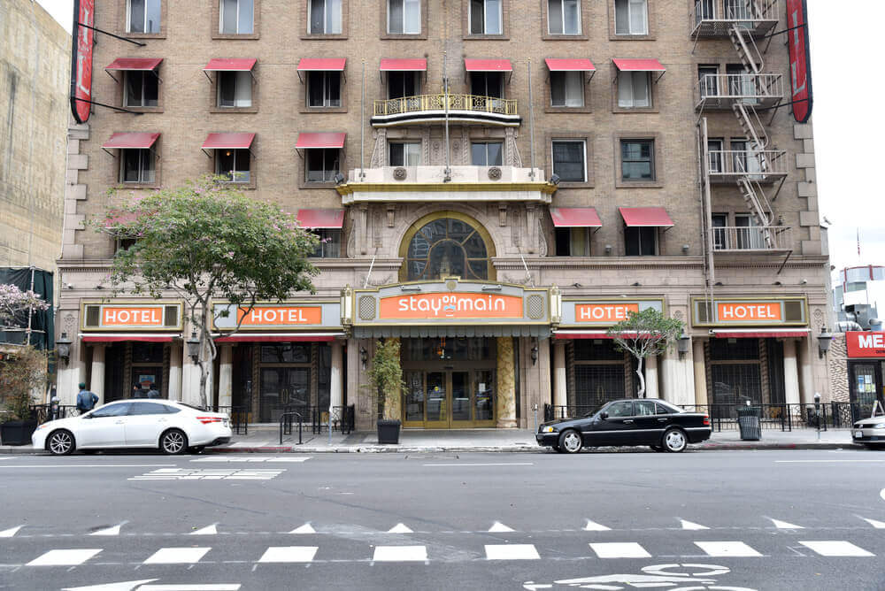The Cecil Hotel is one of the most haunted hotels in the United States. Image of a spooky hotel with updated Stay on Main orange signage.