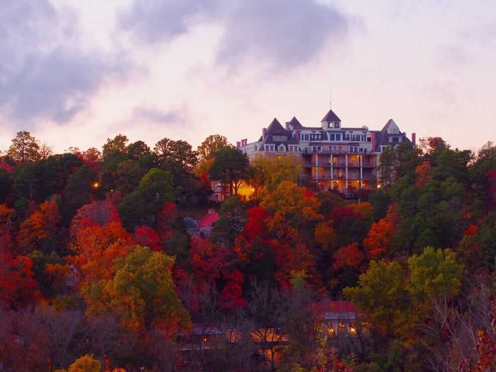 The Crescent Hotel is one of the spookiest Halloween hotels in the United States. Image of a grand hotel sitting on a hill surrounded by trees in fall.