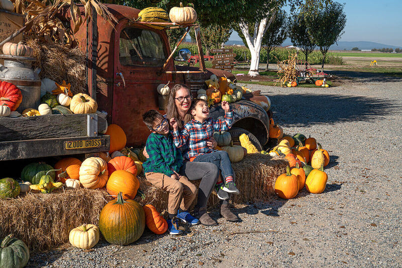 Find out the best photo spots at The Harvest at Tulip Town! Image of a mom and two boys sitting in front of a rusted truck covered with pumpkins.