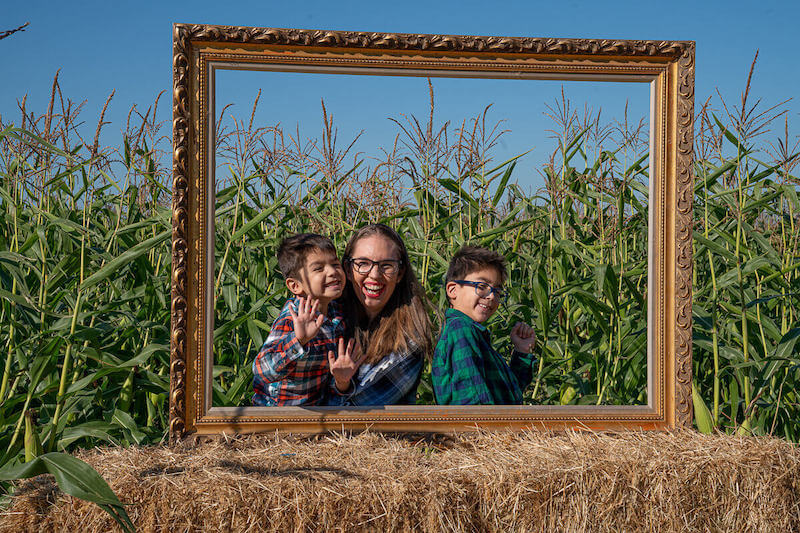 Image of a large empty picture frame with a mom and two boys poking their heads through.
