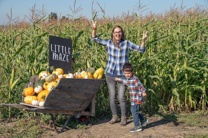 The Harvest at Tulip Town features 2 corn mazes. Image of a mom and boy dancing in front of the little maze sign.