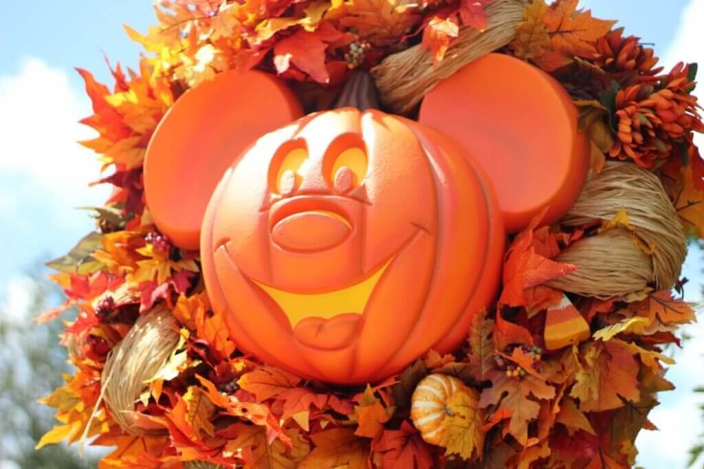 Image of a Mickey Mouse pumpkin surrounded by autumn leaves as Disney Halloween decor.