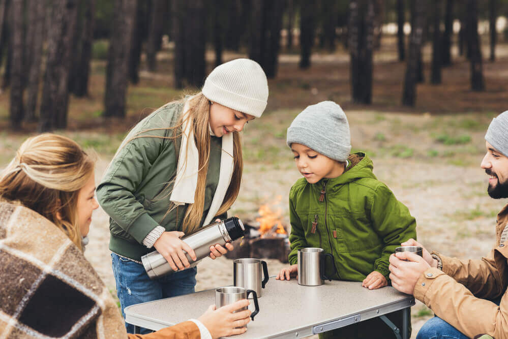 Make sure to check out this fall camping packing list for families so you don't forget anything. Image of a family pouring hot cocoa into thermoses while on a fall camping trip.