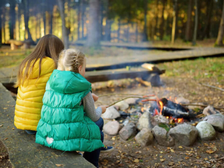 Get my top tips for camping in the fall with kids plus my fall camping packing list for families. Image of two girls roasting marshmallows by the fire.
