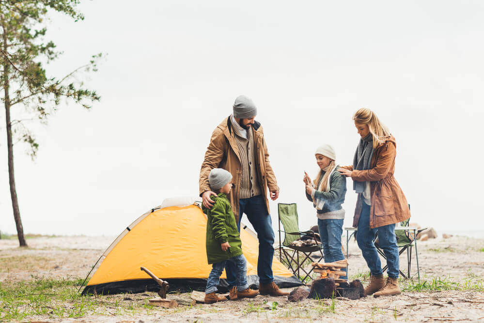 Yes, camping in October can be an awesome fall getaway for families! Image of a family wearing warm clothes by a tent.