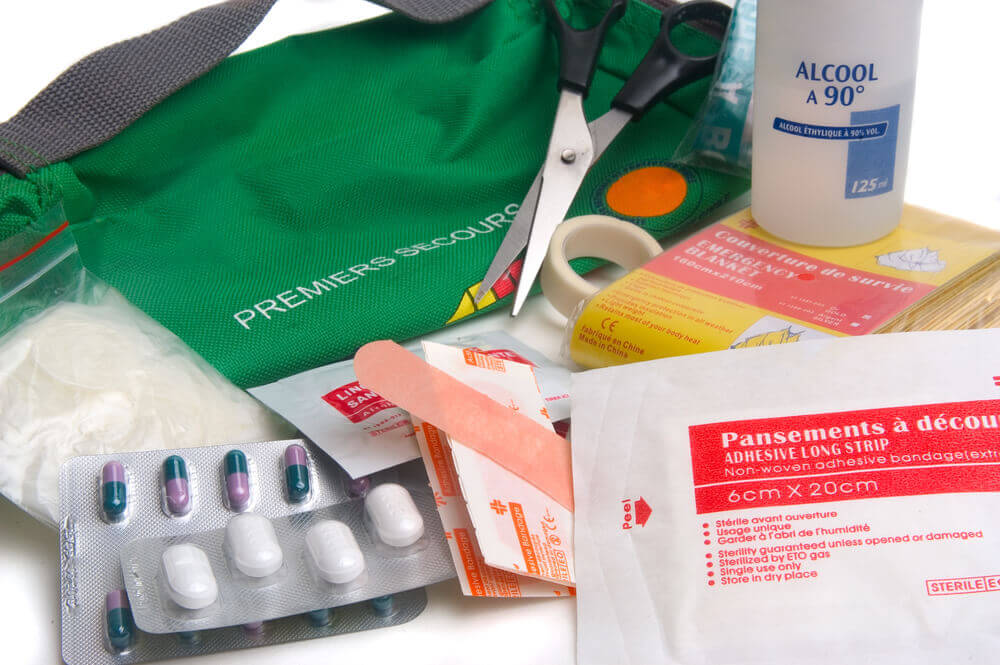 Find out the best things to pack in a first aid kit for kids by top family travel blog Marcie in Mommyland. Image of a bunch of first aid stuff.