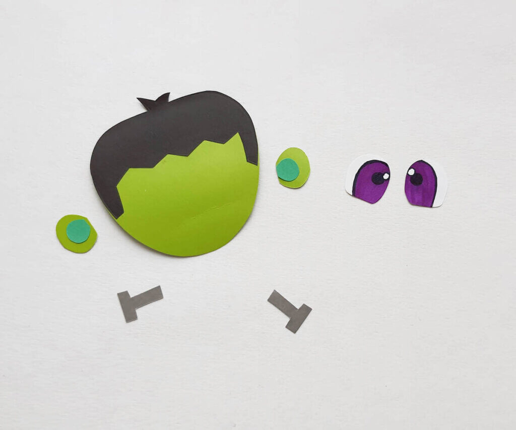 Glue the hair onto the head to make this Frankenstein toilet paper roll craft.