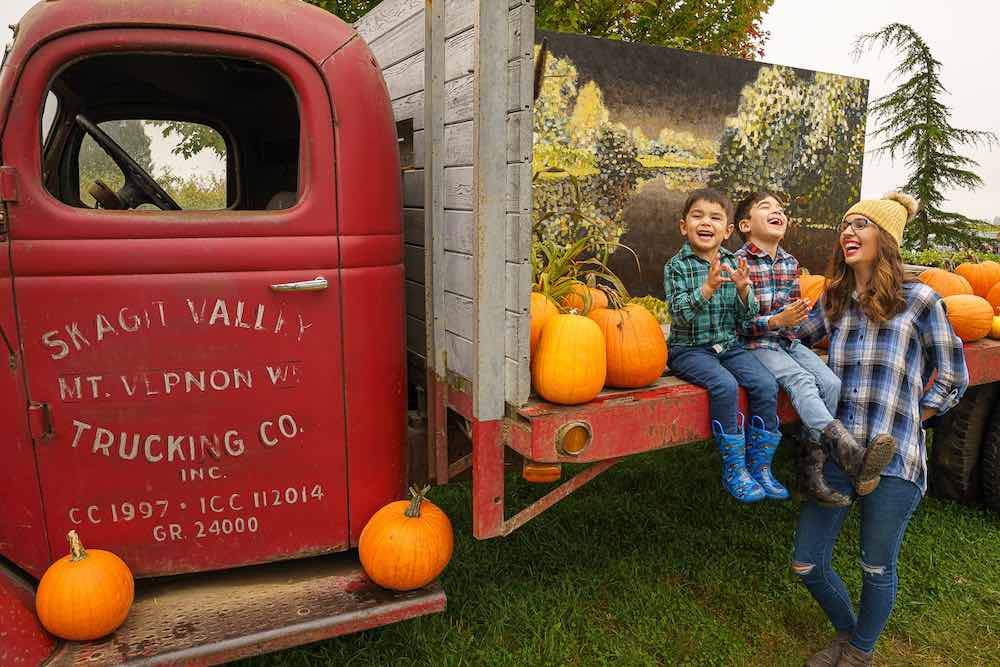Image of a mom and two boys laughing near an old red truck at Gordon Skagit Farms pumpkin patch in Washington State.