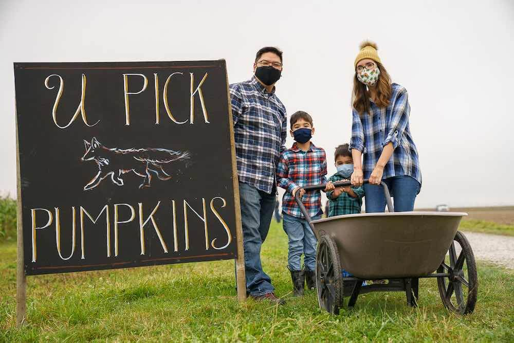 Find out what you need to know about Gordon Skagit Farms by top Seattle blog Marcie in Mommyland. Image of a family wearing plaid holding a wheelbarrown in front of a U Pick Pumpkins sign.
