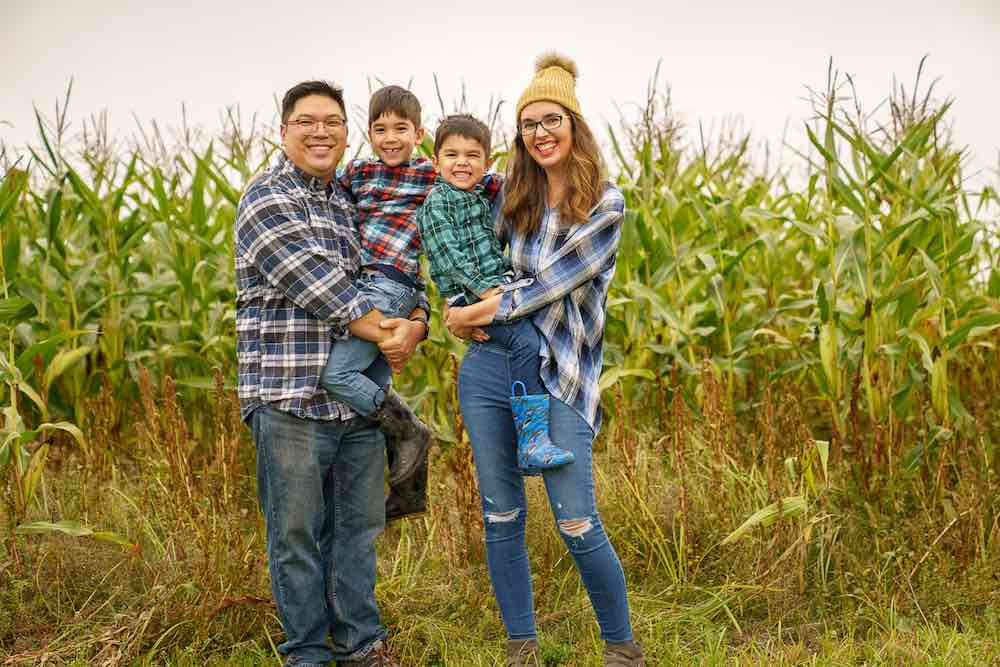 Image of a family wearing plaid standing in front of a cornfield.