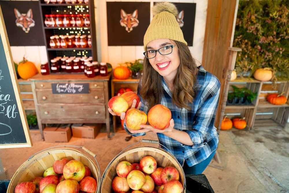 You can find fresh produce at Gordon Skagit Farms, a pumpkin patch near Seattle, WA. Image of a woman holding red apples inside a barn.