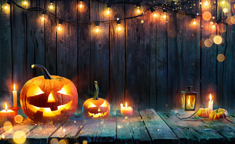 Start off with some simple Halloween outdoor lights. Image of lit Jack-o-lanterns, candles, and string lights.