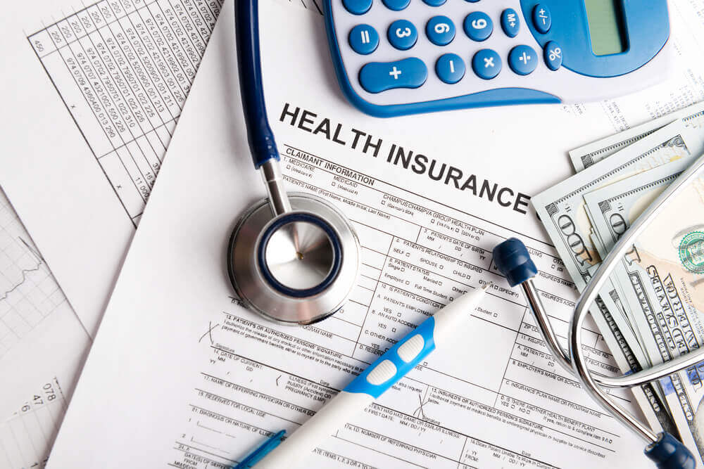It's always good to make sure you have health insurance on your Hawaii vacation. Image of a stethoscope, cash, a calculator, and health insurance forms.
