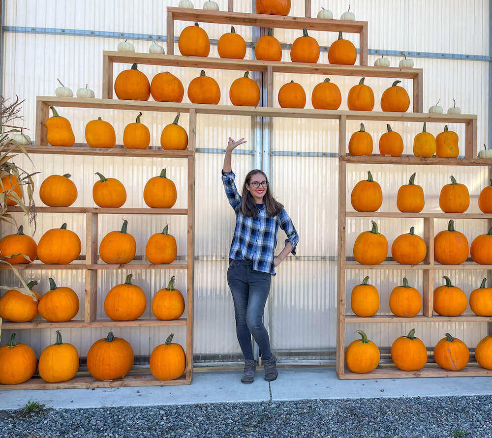 Image of a woman standing in a wall of pumpkins.