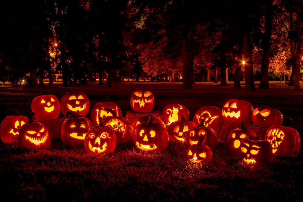 Set out a bunch of jack-o-lanterns with candles inside for a traditional Halloween lighting idea. Image of 21 jack-o-lanterns in a yard.