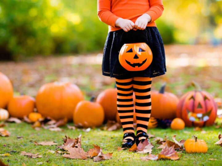 Find out the best non-candy Halloween treats for trick-or-treaters recommended by top Seattle blog Marcie in Mommyland. Image of a girl holding a plastic pumpkin treat container.