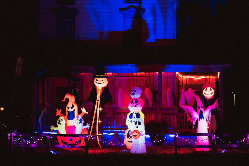 One of the best Halloween lighting ideas is to use inflatables! Image of a porch filled with Halloween inflatables like ghosts, pumpkins, and more.