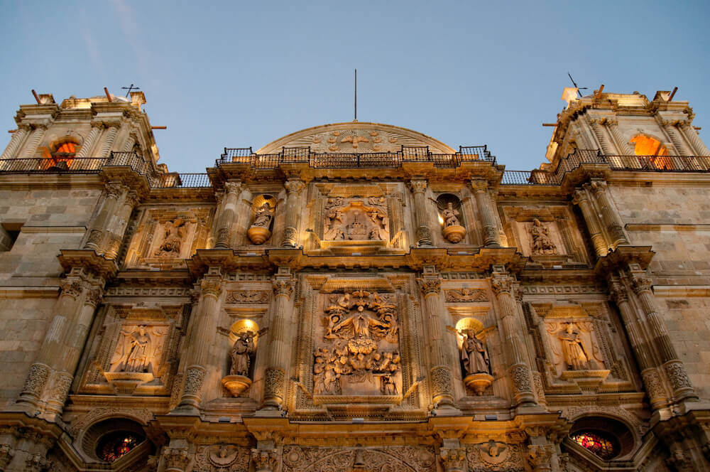 Oaxaca is one of the best small towns in Mexico to celebrate the Day of the Dead. Image of a cathedral lit up at dusk.