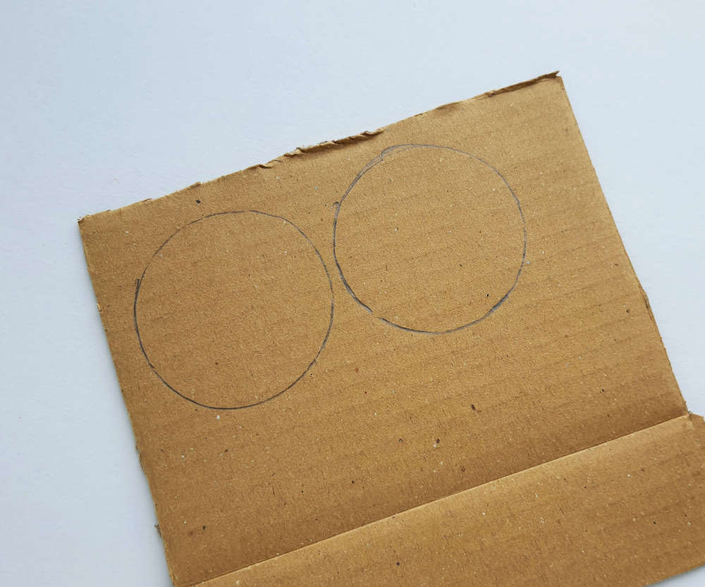 The first step for this Native American craft for kids is to trace circles onto cardboard.