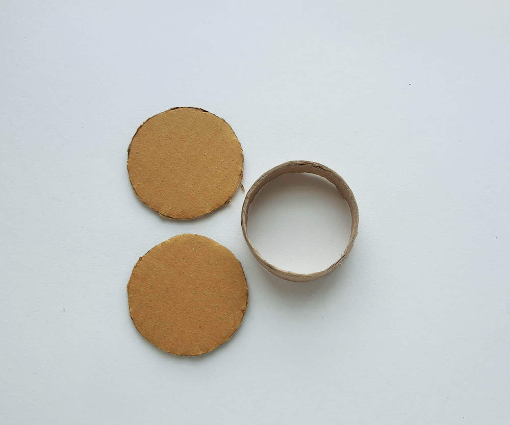 Image of an empty toilet paper roll and two cardboard circles. These are materials to make a spin drum craft.