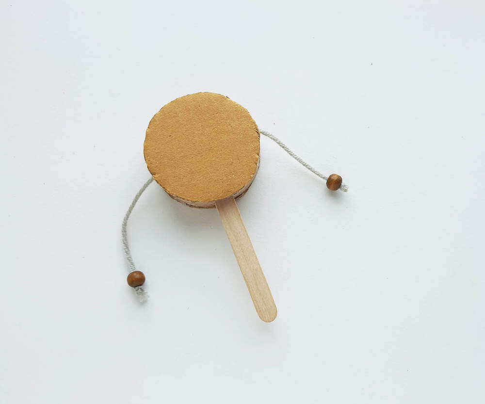 Image of a brown cardboard Native American spin drum craft for kids.