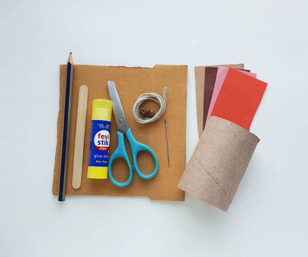 These are the items you'll need for this Native American hand drum craft for kids. Image of a toilet paper roll, craft paper, scissors, glue stick, yarn, beads, a pencil, popsicle stick, and cardboard.