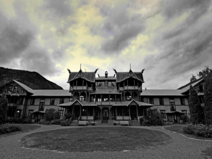 Find out the spookiest Halloween hotels in the United States by top Seattle blog Marcie in Mommyland. Image of a haunted mansion in black and white.