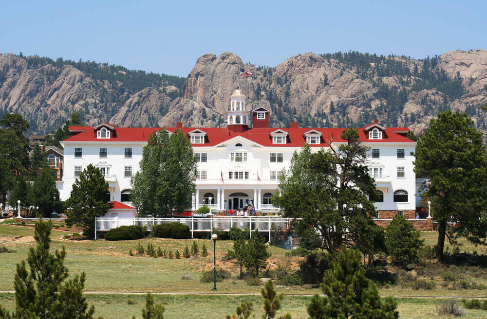 It doesn't get much creepier than the Stanley Hotel in Estes Park, Colorado. Image of a white and red hotel surrounded by dry mountains.